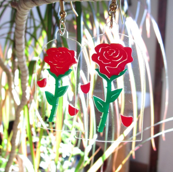 enchanted rose pendant earrings hanging from plant