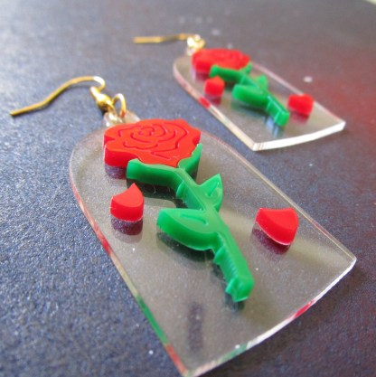 up close side view of beauty and beast enchanted rose earrings with space background