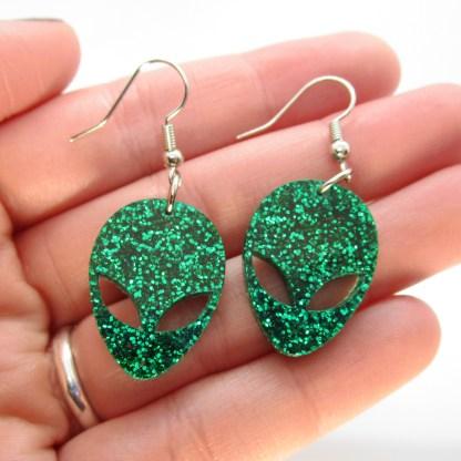 hand holding 2 green glitter alien head dangle earrings