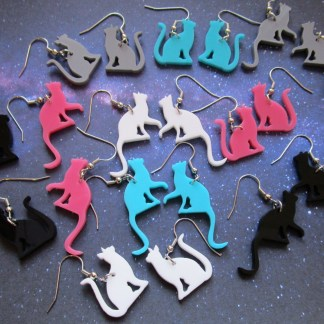 many colors of cat earrings laid out on space background