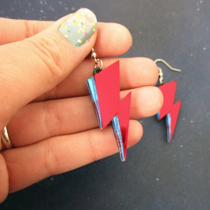 hand holding david bowie lightning red blue earrings