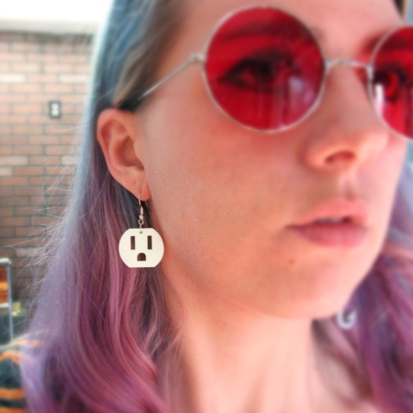 woman wearing weird electrical outlet earring with red glasses on