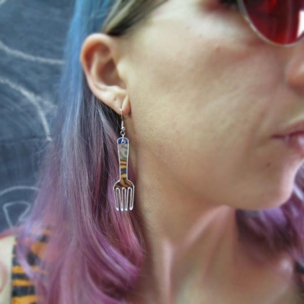 woman in red glasses wearing fork dangle earring