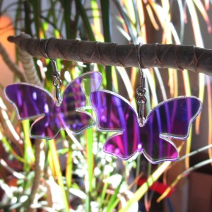Iridescent Butterfly Wings Dangle Earrings with plants in background