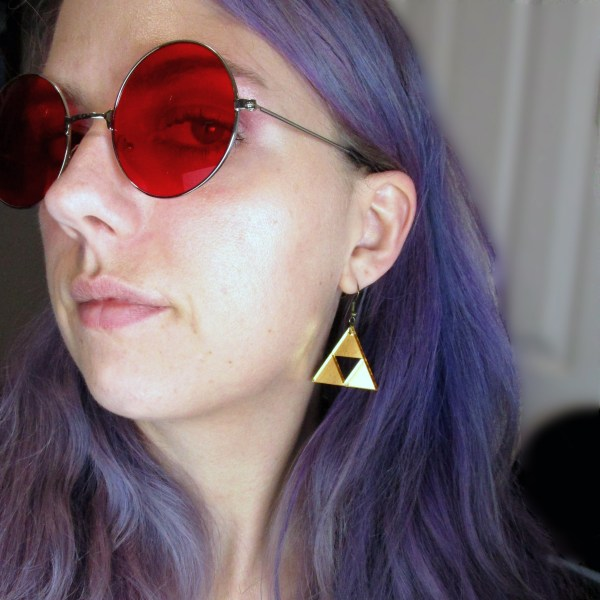 lady wearing triforce dangle earrings with red glasses on
