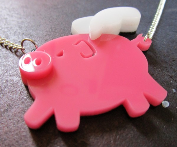 side close up shot of pink flying pig pendant necklace