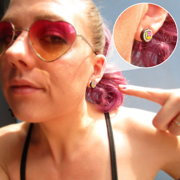 woman wearing Mini Sushi Roll Earring pointing to earring with zoom in feature