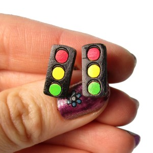 hand holding traffic light symbol earrings to show size