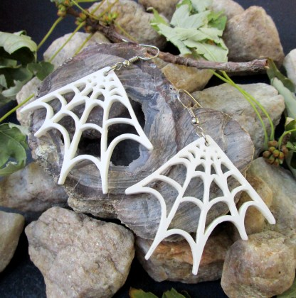 white spider web earrings on rocks