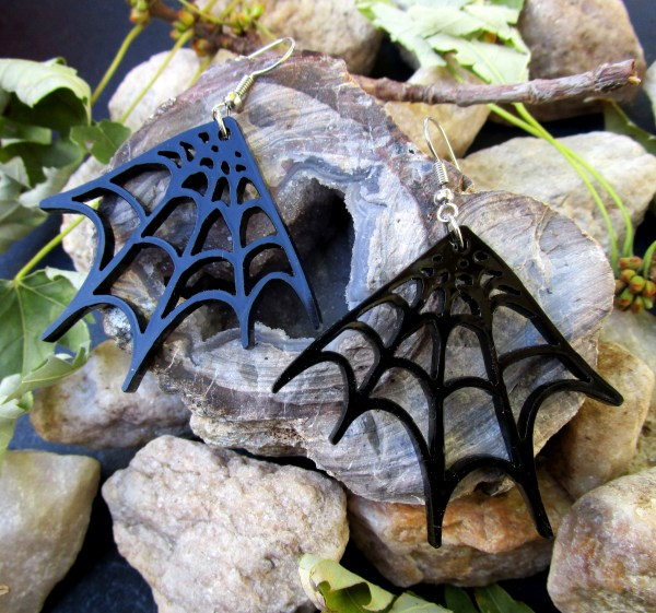 black corner spider web earrings on rocks