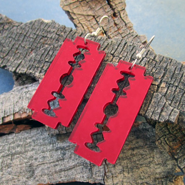 red double sided razor blade earrings on wood