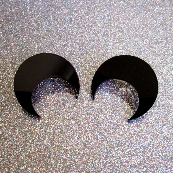 black crescent moon earring shapes on glitter paper