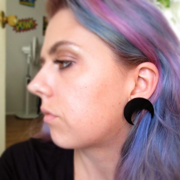 lady wearing large black crescent moon earring in ear