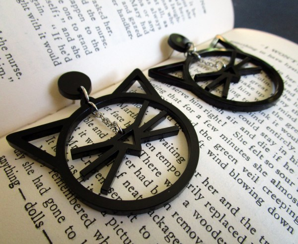 close up of line art cat face dangle earrings on book pages