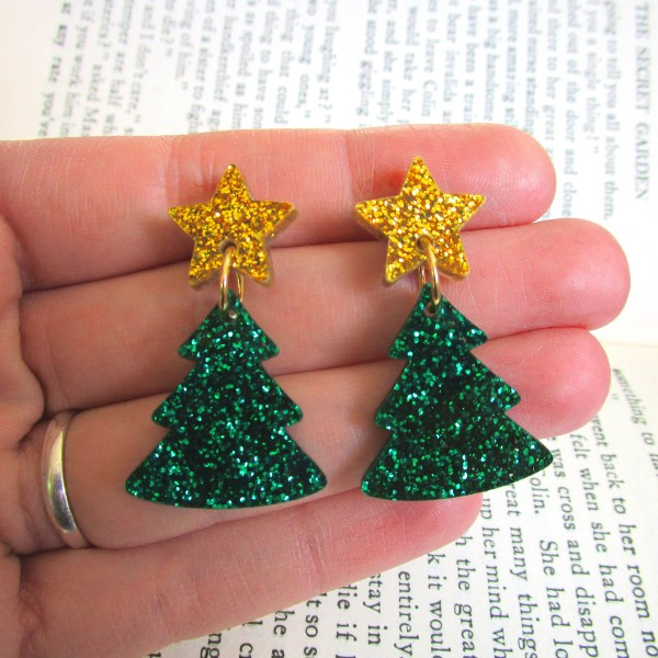 hand holding xmas tree earrings over book
