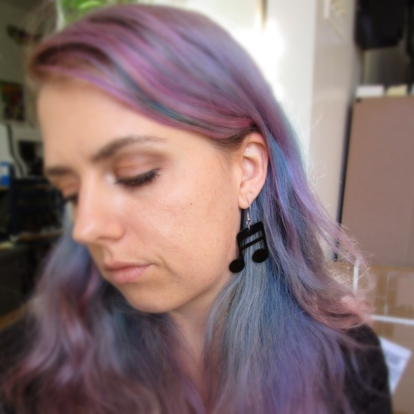 lady wearing large music note earrings
