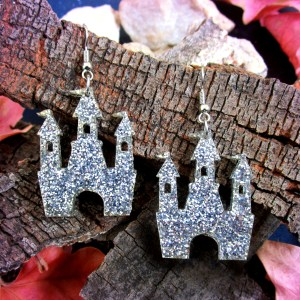 silver glitter castle shaped earrings on wood background