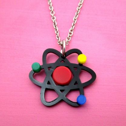 atom pendant necklace on pink background