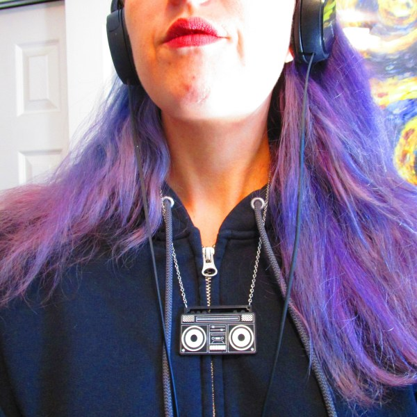 purple hair lady wearing boom box necklace and hoodie