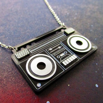 close up of laser cut acrylic boom box radio pendant necklace