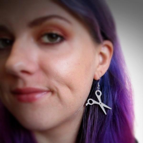 lady wearing silver scissor pendant statement ddangle earrings
