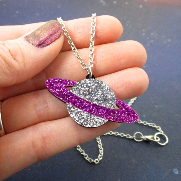 hand holding glitter planet necklace