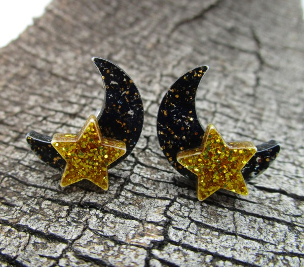 black glitter and gold glitter moon and star stud earrings on wood