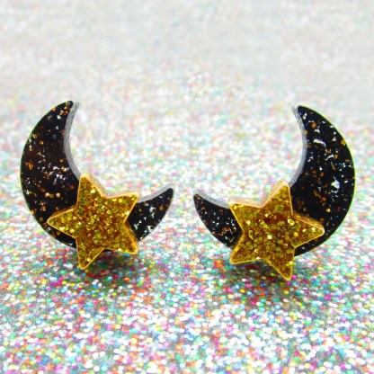 glitter surface with black and gold moon and star earrings