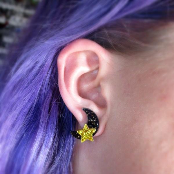 ear wearing black and gold star moon earrings stud