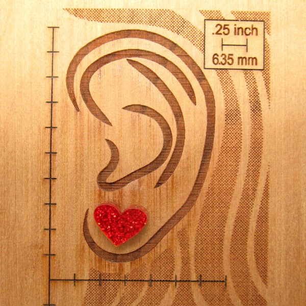 minimalist glitter heart stud earrings on display board with ear to show size