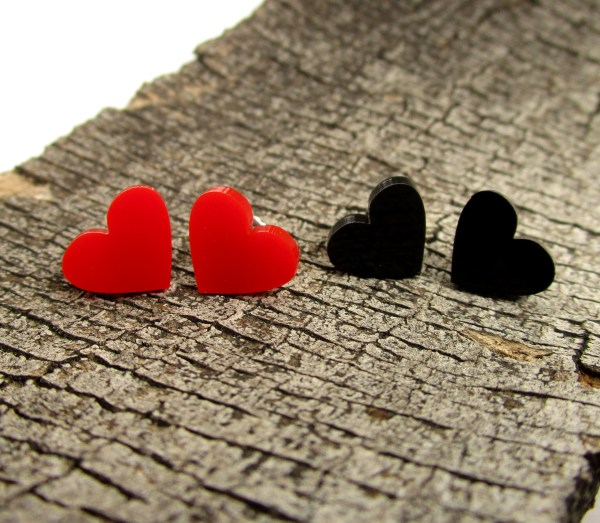 pair of red and black heart stud earrings on wood background