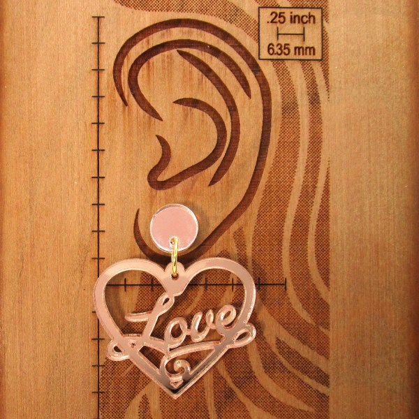 ear image with love heart stud earrings to show size and dimention
