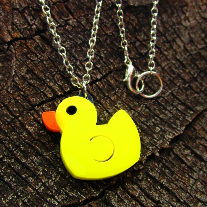 yellow rubber duck necklace on wood background