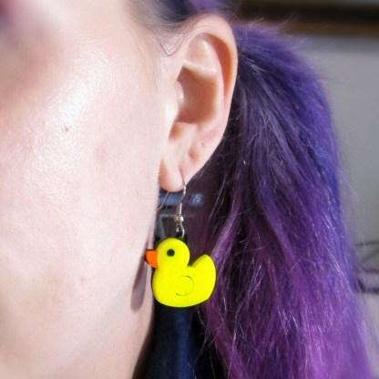 purple hair lady wearing yellow rubber duck dangle earring in ear