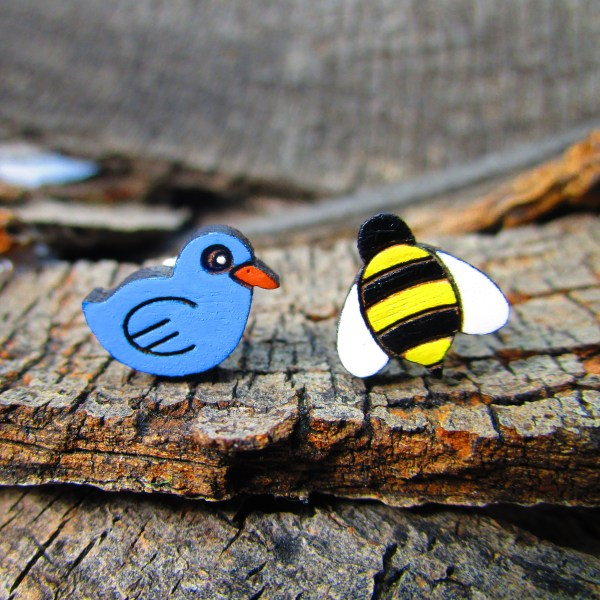blue bird and cartoon bee mismatch earring set on wood