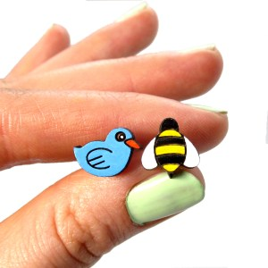 hand holding birds and bees earrings set