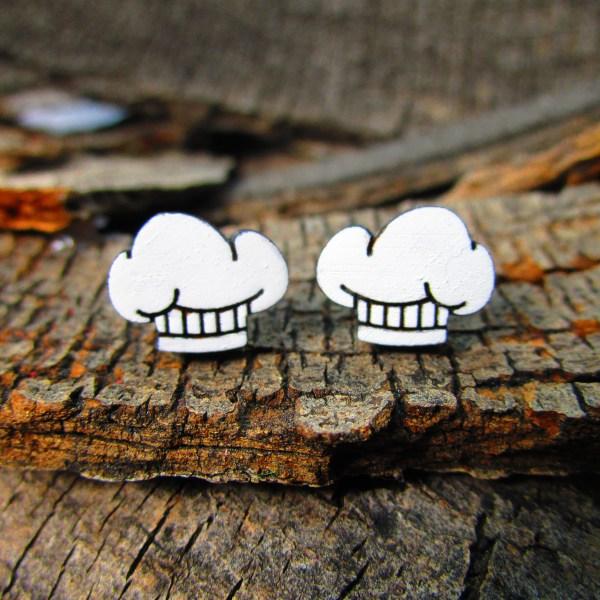 cute little chef hat stud earrings on wood background