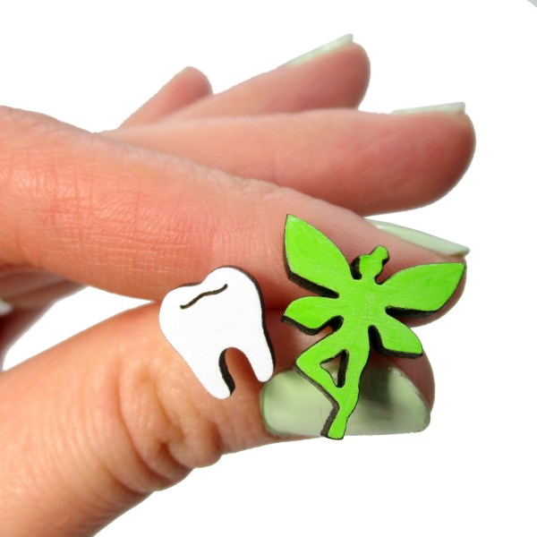 hand holding tooth fairy green stud earrings to show size