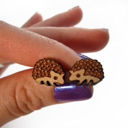 hand holding wood hedgehog earrings to show size