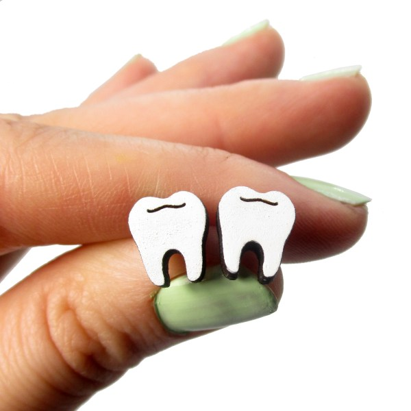 hand holding pair of wisdom teeth earrings to show size