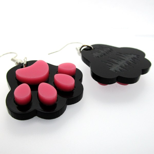 black paw print dangle earrings on side to show raised detail