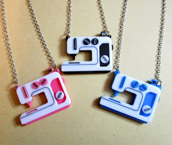 3 sewing embroidery machine pendant necklaces on kraft paper