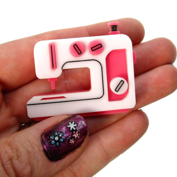 hand holding pink sewing machine pin brooch to show size