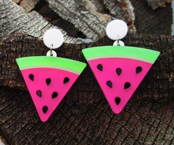 pair of watermelon seed slice stud dangle earrings on wood background