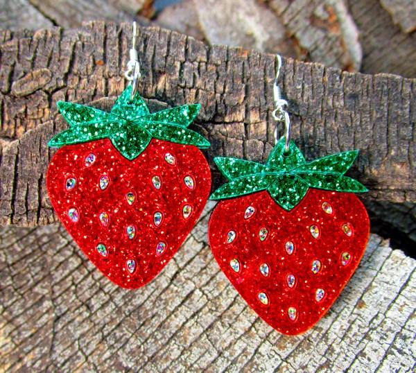 red strawberry glitter dangle earrings on wood background