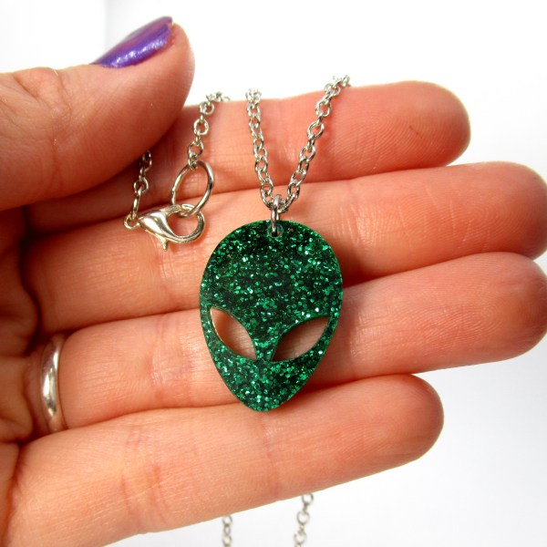 hand holding alien pendant necklace to show size