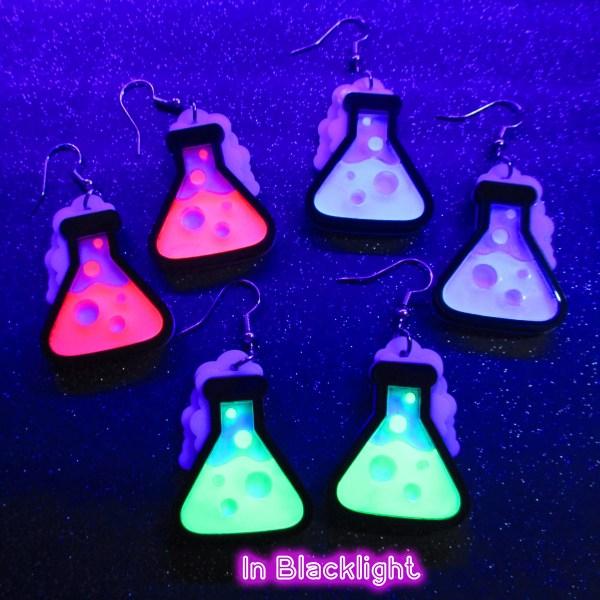 neon beaker pendant earrings under black light to show glowing effect