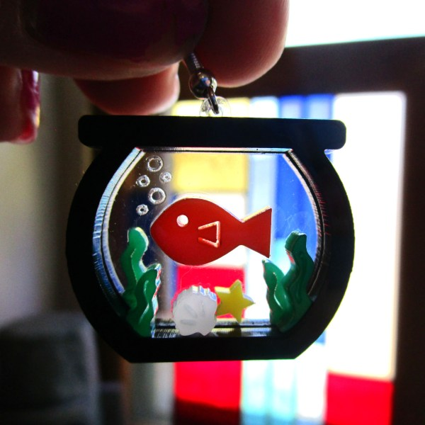 hand holding laser cut fish in aquarium close up to show detail