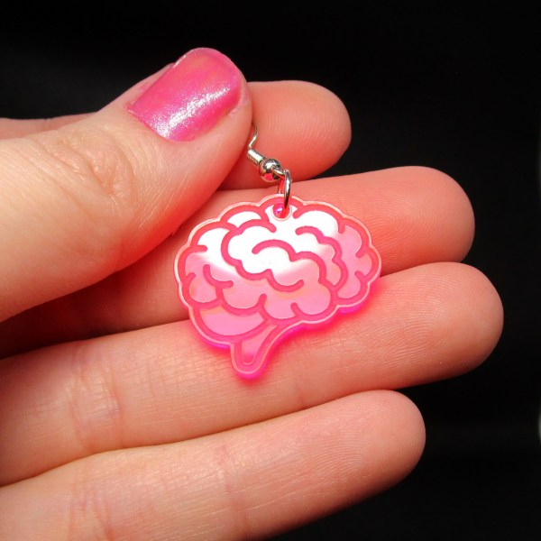 hand holding shiny pink brain charm earring to show size