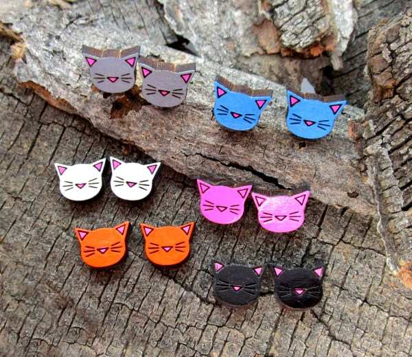 multiple handmade cat stud earring of different colors on wood background